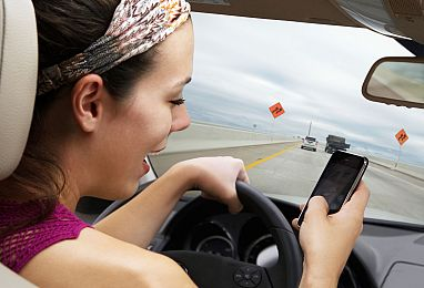 Photo of person texting while driving